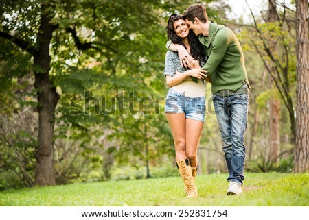 Young cheerful couple, attractive brunette and her handsome boyfriend, embracing and smiling walking through the park. - stock photo