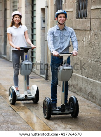 Young cheerful couple driving a segways and smiling. Focus on man  - stock photo