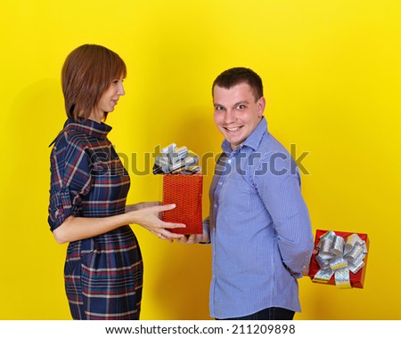 Young cheerful couple gives each other gifts for the holiday - stock photo