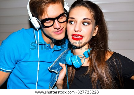 Young cheerful couple going crazy together, emotional funny faces, urban party, listening music at stylish big  headphones, hipster couple in love. - stock photo