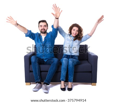young cheerful couple sitting on sofa and watching football isolated on white background - stock photo