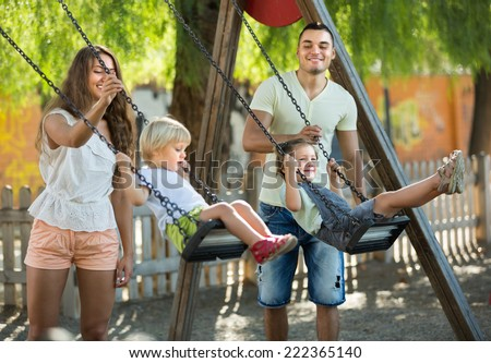 Young cheerful family of four at playground's swings. Focus on girl  - stock photo