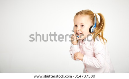 Young cheerful female customer support operator with headset and smiling - stock photo