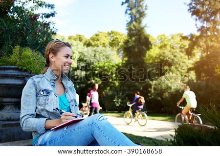 Young cheerful female is looking on something funny while is sitting with her diary in park in warm spring day, happy smiling woman is enjoying leisure and rest during long awaiting weekend overseas - stock photo