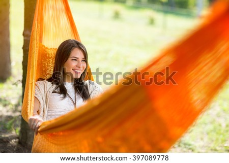 Young cheerful female lying down in orange hammock and resting in nature - stock photo