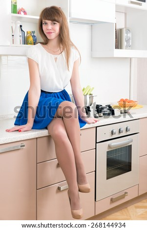 Young cheerful female sitting on the top of kitchen counter. Uncooked meal on the background. - stock photo