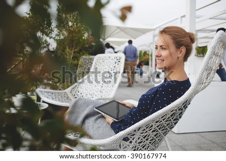 Young cheerful female student is enjoying free time,while is sitting with touch pad in coffee shop outdoors. Beautiful woman is holding digital tablet and smiling for someone during rest in cafe-bar - stock photo