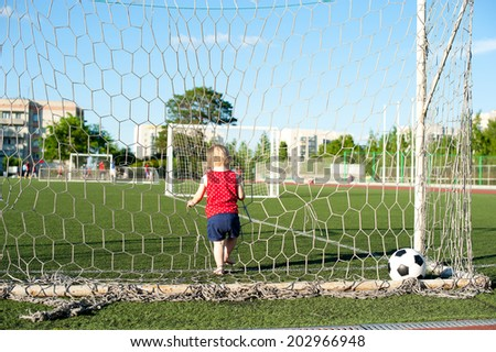 Young cheerful football fan girl on fresh green grass with ball  - stock photo