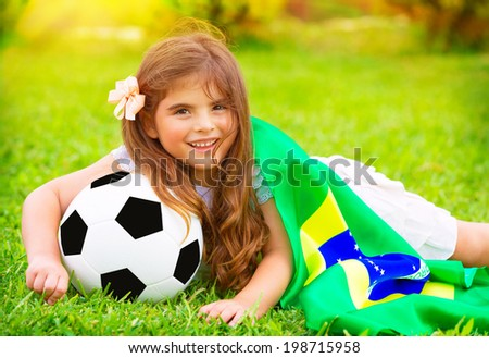 Young cheerful football fan lying down on fresh green grass with ball and big Brazil flag, happy supporter of Brazilian football team - stock photo