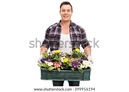 Young cheerful gardener holding a plastic crate full of beautiful flowers isolated on white background - stock photo