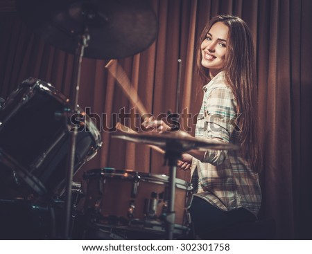 Young cheerful girl behind drums on a rehearsal  - stock photo