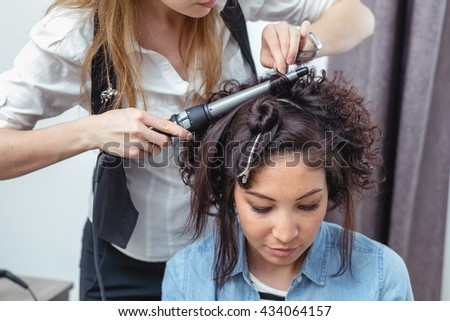 Young cheerful girl doing hairstyle in a barbershop.