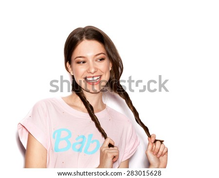 Young cheerful girl having fun. Smiling Woman with bright makeup and hairstyle with pigtails. White background not isolated - stock photo