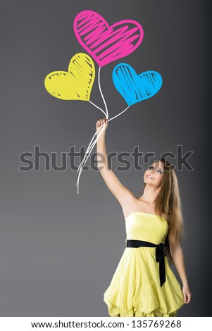 Young cheerful girl hold hand-drawn colored hearts balloons - stock photo