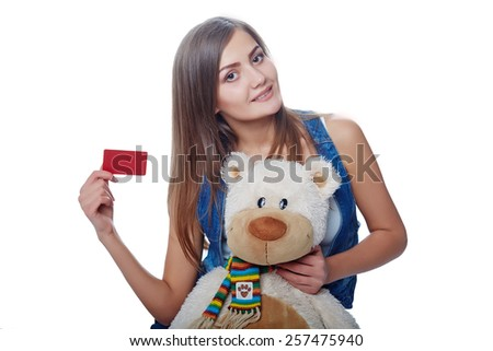 Young cheerful girl holding big soft toy bear and card of the bank credit isolated on white - stock photo