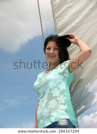 young cheerful girl in a baseball cap next to the sail against the blue sky - stock photo