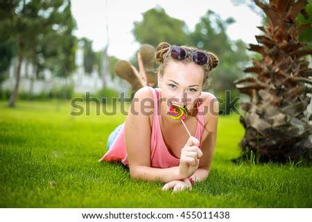 Young cheerful girl in a pink top and denim shorts with a lollipop in his hand lying on green grass
