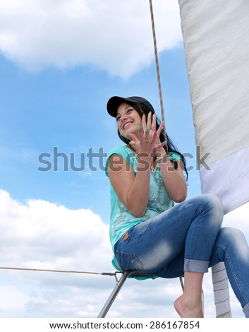 young cheerful girl in jeans and a baseball cap near the sail against the blue sky