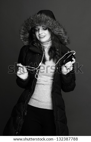 Young cheerful girl in warm jacket with headphones - stock photo