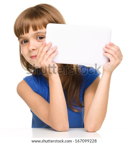 Young cheerful girl is hiding behind tablet while sitting at table, isolated over white - stock photo