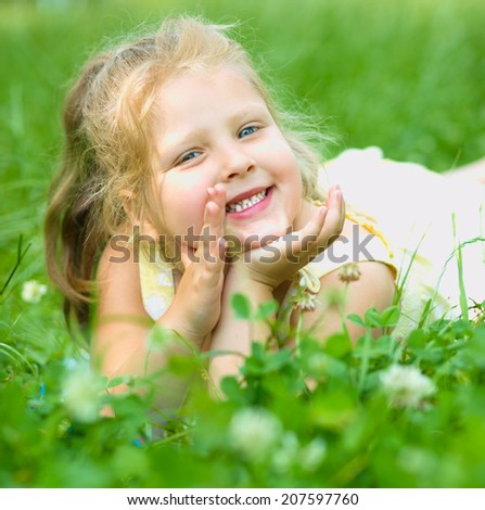 Young cheerful girl is playing outdoors