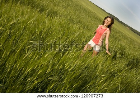Young cheerful  girl is running on the field