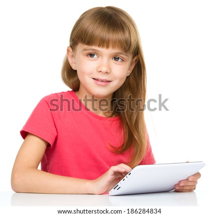 Young cheerful girl is using tablet while sitting at table, isolated over white