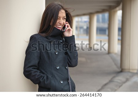 Young cheerful girl talking on the phone. - stock photo