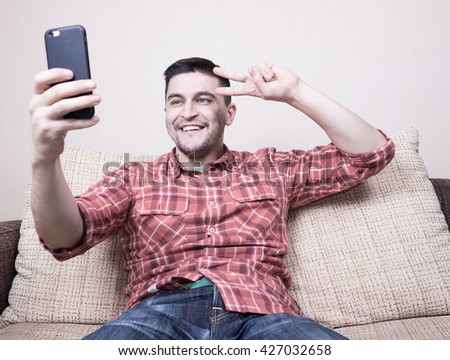 Young cheerful guy doing selfie on smartphone and sitting on sofa