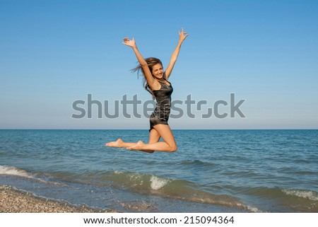 Young cheerful  happiness girl on sea Beach jumping or dancing - stock photo
