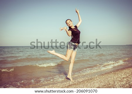 Young cheerful  happiness girl on the Bathing Beach jumping and dancing