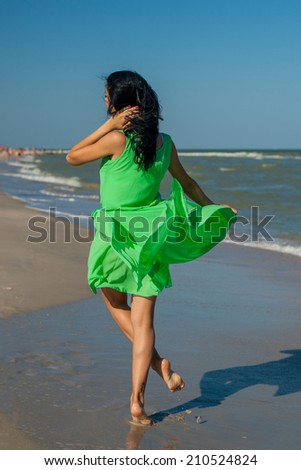 Young cheerful  happiness girl on the Bathing Beach jumping and dancing - stock photo