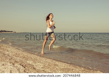 Young cheerful  happiness girl  runs on the Bathing Beach