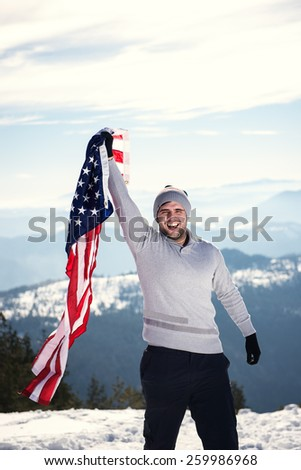 Young cheerful happy man holding USA flag on the top of the mountain with one hand. Copy space on the top, overexposed highlights - stock photo