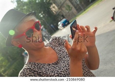 Young Cheerful Hipster Girl In Park Using Smart Phone - stock photo