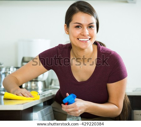 Young cheerful housewife with rag and cleanser cleaning up - stock photo