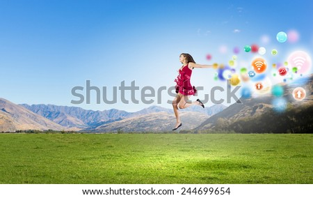 Young cheerful lady in red dress jumping high
