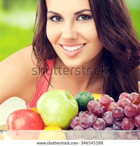 Young cheerful lovely brunette woman with plate of fruits, outdoors. Healthy eating, beauty and dieting concept. - stock photo