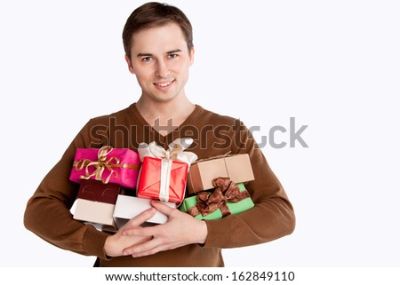 young cheerful man holding many gifts - stock photo
