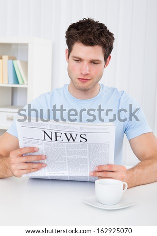 Young cheerful man reading newspaper at home - stock photo