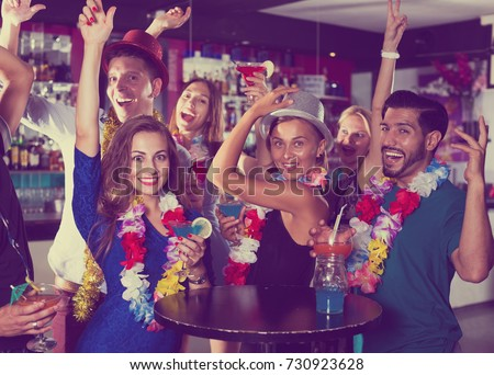 Young cheerful men and women dancing on the hawaiian party