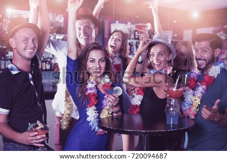 Young cheerful men and women dancing on the hawaiian party in nightclub