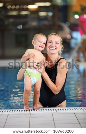 Young cheerful mother and little son in a swimming pool - stock photo