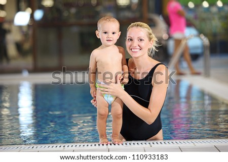 Young cheerful mother and little son looking at the camera at the edge of a swimming pool