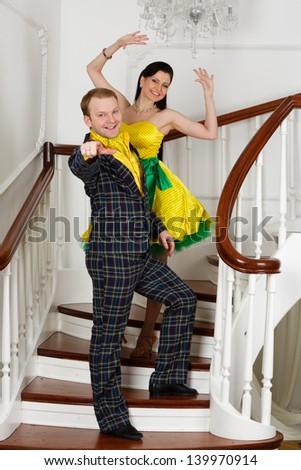 Young cheerful pair in bright clothes of style of a retro on a ladder in a room.