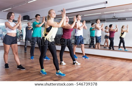 Young cheerful people dancing zumba elements in dancing class