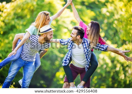 Young cheerful people piggybacking in the park during springtime - stock photo