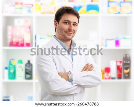 Young cheerful pharmacist chemist standing in retail drug store. Handsome male doctor wearing uniform selling drugs. - stock photo