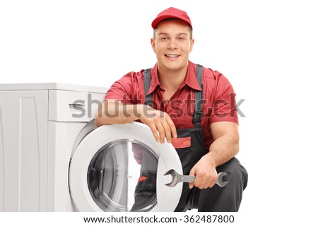 Young cheerful plumber holding a wrench and posing next to a washing machine isolated on white background