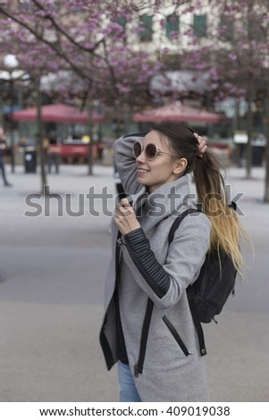 young cheerful scandinavian woman playing with her hair wearing round eyeglasses in the park in european city while tress blossoming
